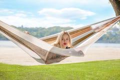 Молодая белокурая женщина отдыхая на гамаке стоковое фото rf