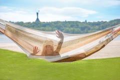 Молодая белокурая женщина отдыхая на гамаке стоковые фото