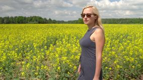 Молодая белокурая женщина представляя в красивом поле рапса видеоматериал