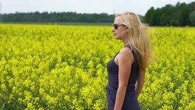 Молодая белокурая женщина представляя в красивом поле рапса сток-видео