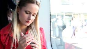 Молодая белокурая женщина сидя в трамвае, держа чернь, телефон, клетка акции видеоматериалы