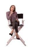 Молодая белокурая женщина сидя на стуле и держа ее руку под ее подбородком стоковое изображение