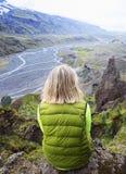 Молодая белокурая женщина сидя на уступе горы Стоковые Изображения RF