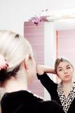 Молодая белокурая женщина смотря к зеркалу и расчесывая ее волосы стоковая фотография rf