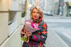 Молодая белокурая женщина с букетом цветков на улице города Стоковое Изображение RF