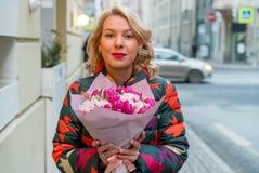 Молодая белокурая женщина с букетом цветков на улице города Стоковые Фото