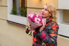 Молодая белокурая женщина с букетом цветков на улице города Стоковая Фотография
