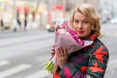 Молодая белокурая женщина с букетом цветков на улице города Стоковое Фото