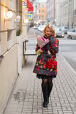 Молодая белокурая женщина с букетом цветков на улице города Стоковые Изображения RF
