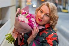 Молодая белокурая женщина с букетом цветков на улице города Стоковая Фотография RF