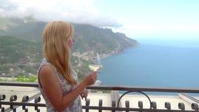 Молодая белокурая женщина с вином в ресторане на Ravello видеоматериал