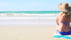 Молодая белокурая женщина с голубыми бикини и соломенной шляпой сидит на пляже и смотрит море видеоматериал