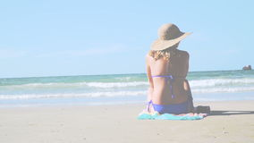 Молодая белокурая женщина с голубыми бикини и соломенной шляпой сидит на пляже и смотрит море акции видеоматериалы