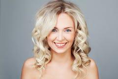 Молодая белокурая женщина с усмехаться вьющиеся волосы Стоковые Изображения