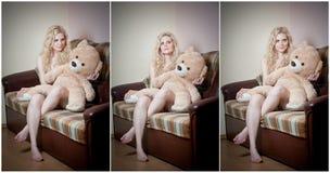 Молодая белокурая чувственная женщина сидя на софе ослабляя с огромным плюшевым медвежонком Стоковое фото RF