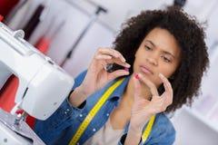 Молодая белошвейка на работе в фабрике Стоковая Фотография