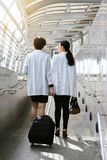 Молодая бизнес-леди вытягивая чемодан пока идущ через мост восхождения на борт пассажира стоковая фотография