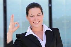 Молодая бизнес-леди в черном костюме показывая о'кеы стоковые изображения rf