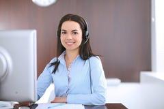Молодая бизнес-леди в шлемофоне, сидя на таблице в офисе Стоковая Фотография