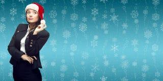 Молодая бизнес-леди в шляпе santa стоя над backgroun зимы Стоковые Фотографии RF