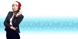 Молодая бизнес-леди в шляпе santa стоя над backgroun зимы Стоковые Изображения RF