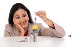 Молодая бизнес-леди держа ключ формы дома Стоковое Изображение RF