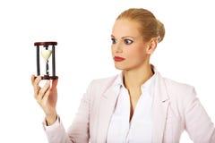 Молодая бизнес-леди держа часы белизна времени предмета предпосылки изолированная принципиальной схемой стоковое изображение rf