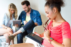 Молодая бизнес-леди используя ее таблетку, на заднем плане шину Стоковые Изображения RF