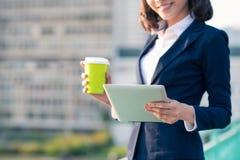 Молодая бизнес-леди используя таблетку в улице с бушелем офиса Стоковая Фотография RF