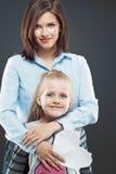 Молодая бизнес-леди при девушка ребенка стоя против серого цвета Стоковая Фотография