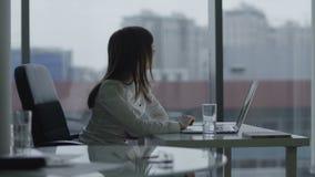 Молодая бизнес-леди работая на компьтер-книжке в современном офисе она усмехаясь и принимает пролом акции видеоматериалы