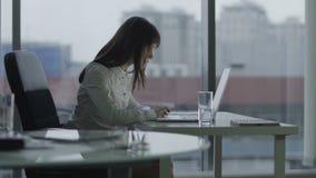 Молодая бизнес-леди работая на компьтер-книжке в современном офисе она сфокусировала и серьезный акции видеоматериалы