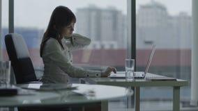Молодая бизнес-леди работая на компьтер-книжке в современном офисе она останавливает потому что задние повреждения акции видеоматериалы