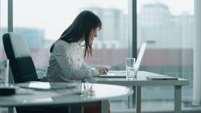 Молодая бизнес-леди работая на компьтер-книжке в современном офисе она сфокусировала и серьезный видеоматериал