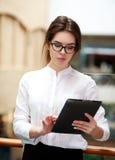 Молодая бизнес-леди работая на таблетке стоя крытый Стоковое фото RF