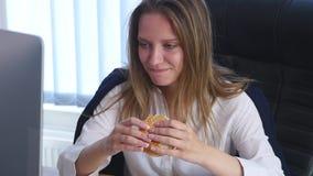 Молодая бизнес-леди сидя в офисе и есть бургер Стоковое Фото