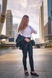 Молодая бизнес-леди смотря вахту как ждать назначение Стоковое Изображение RF