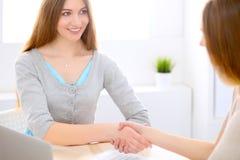 Молодая бизнес-леди тряся руки сидя на столе Стоковые Изображения RF