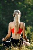 Молодая блондинка в красном верхе сидит на траве для фитнеса в природе Спортсменка подготавливает для гимнастики Стоковые Фото