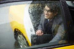Молодая дверь такси отверстия бизнесмена в дожде Стоковое Фото
