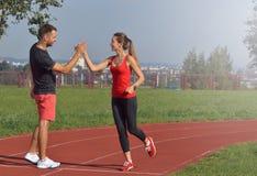 Молодая взрослая женщина давая максимум 5 к партнеру после бега Стоковые Фото
