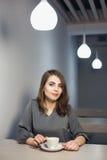 Молодая взрослая женщина имеет перерыв на чашку кофе в кафе; Стоковые Фото
