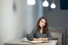 Молодая взрослая женщина имеет перерыв на чашку кофе в примечаниях кафа и сочинительства в дневнике или блокноте; Стоковая Фотография RF