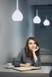 Молодая взрослая женщина имеет перерыв на чашку кофе в примечаниях кафа и сочинительства в дневнике или блокноте; Стоковые Фотографии RF