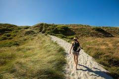 Молодая взрослая женщина идя на след песка на пляже Wharariki Стоковые Фото