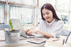 Молодая вскользь азиатская женщина используя технологию Стоковое Изображение RF