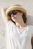Молодая вскользь девушка нося шляпу и солнечные очки ослабила Стоковое Изображение