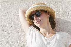Молодая вскользь девушка нося шляпу и солнечные очки ослабила Стоковое фото RF