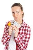 Молодая вскользь женщина держа пилюльки. Стоковые Изображения RF