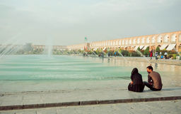 Молодая встреча пар и говорить около фонтана популярного квадрата имама в Isfahan Стоковые Фото